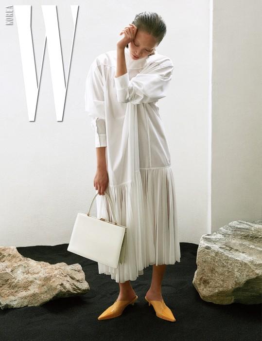 순백의 플리츠 드레스와 클래식한 분위기의 사각 토트백, 진주 귀고리, 포인티드 토가 돋보이는 노란색 뮬은 모두 Celine 제품.