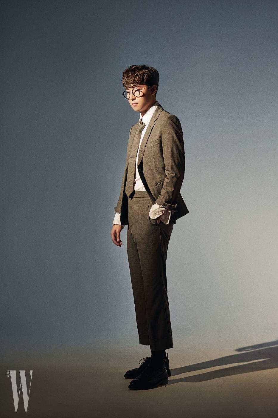 권순관이 입은 화이트 셔츠, 넥타이와 핀, 그레이 슈트, 슈즈는 모두 톰 브라운, 안경은 마스카 제품.