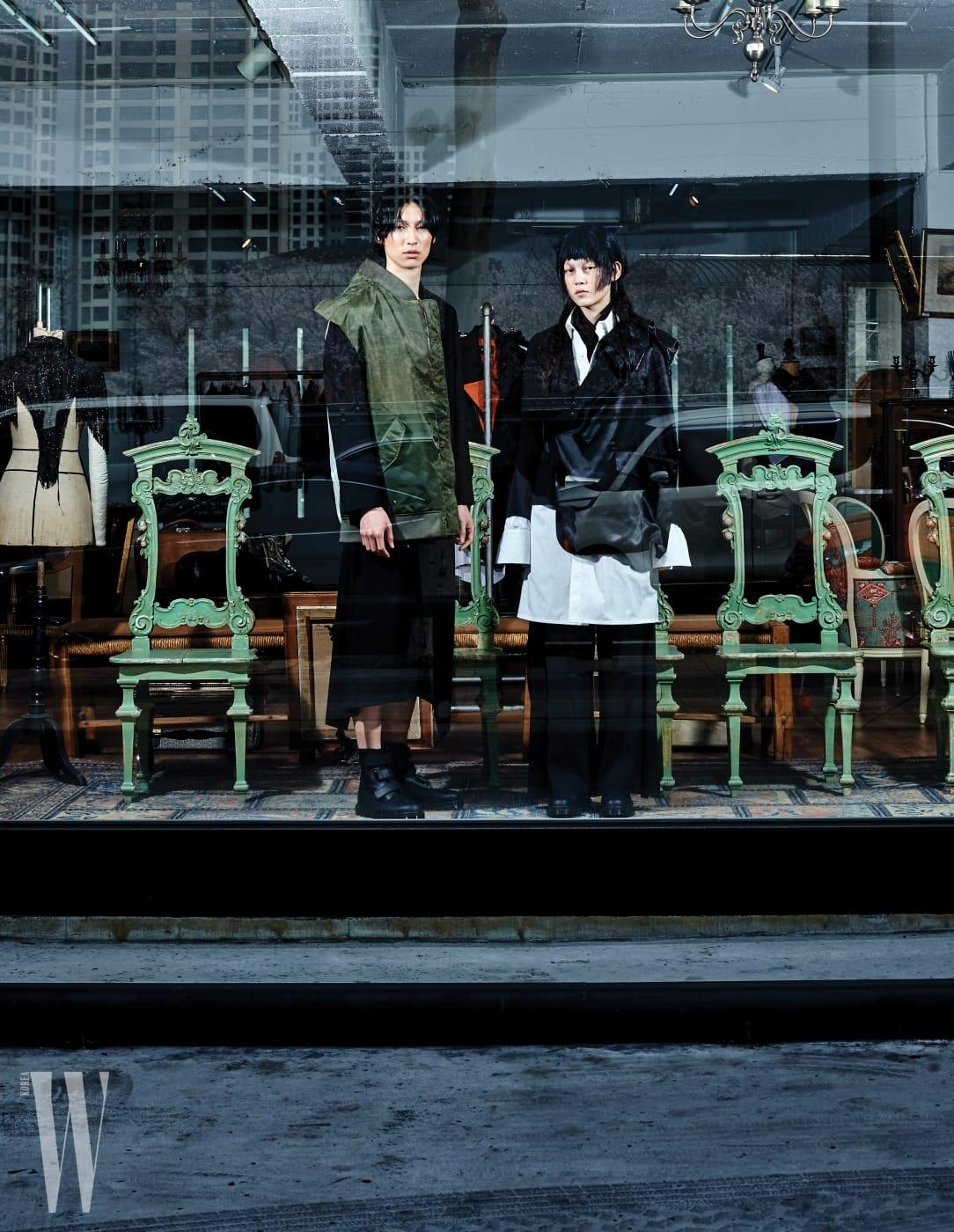 테이가 입은 항공점퍼와 테일러드 재킷의 디테일이 조합된 아우터, 검은색 팬츠, 검정 워커, 정청솔이 입은 오버사이즈 셔츠와 테일러드 재킷, 와이드 팬츠, 워커는 모두 Moo Hong 제품.