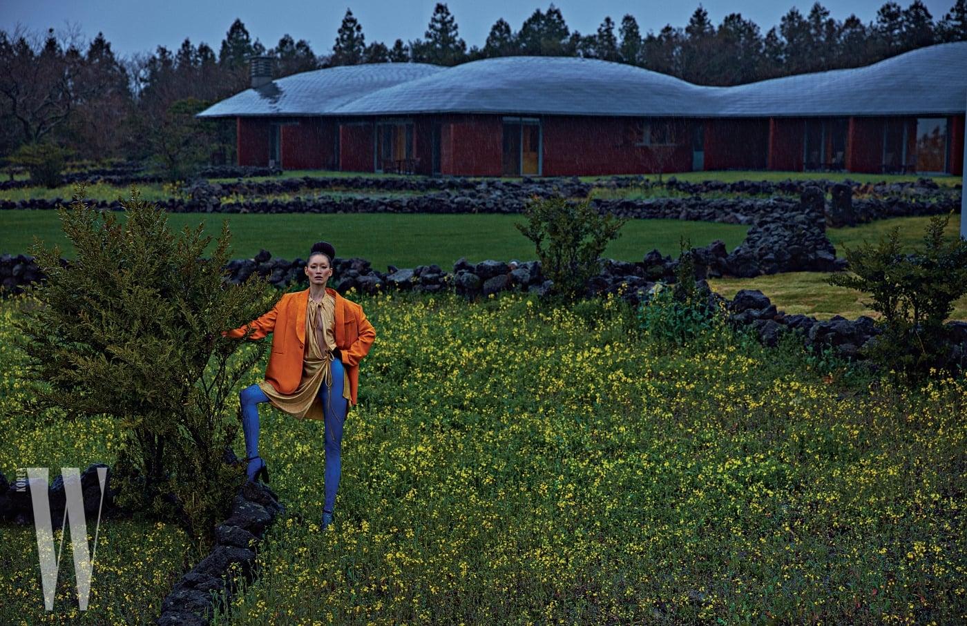 주황색 턱시도 재킷과 실크 드레스, 푸른색 타이츠, 장갑과 샌들은 모두 Balenciaga 제품.
