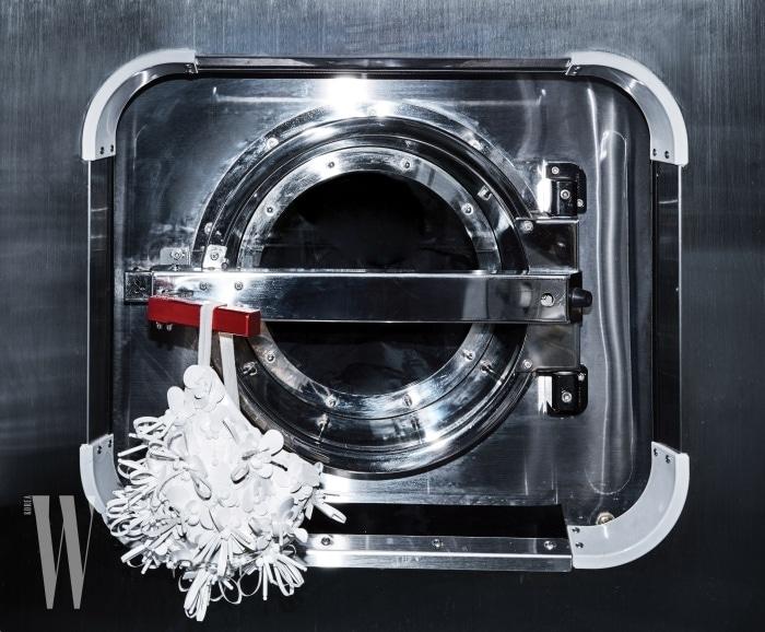 메탈릭한 세탁기에 걸려 있는 꽃 장식 수영 모자는 미우미우 제품. 가격 미정.