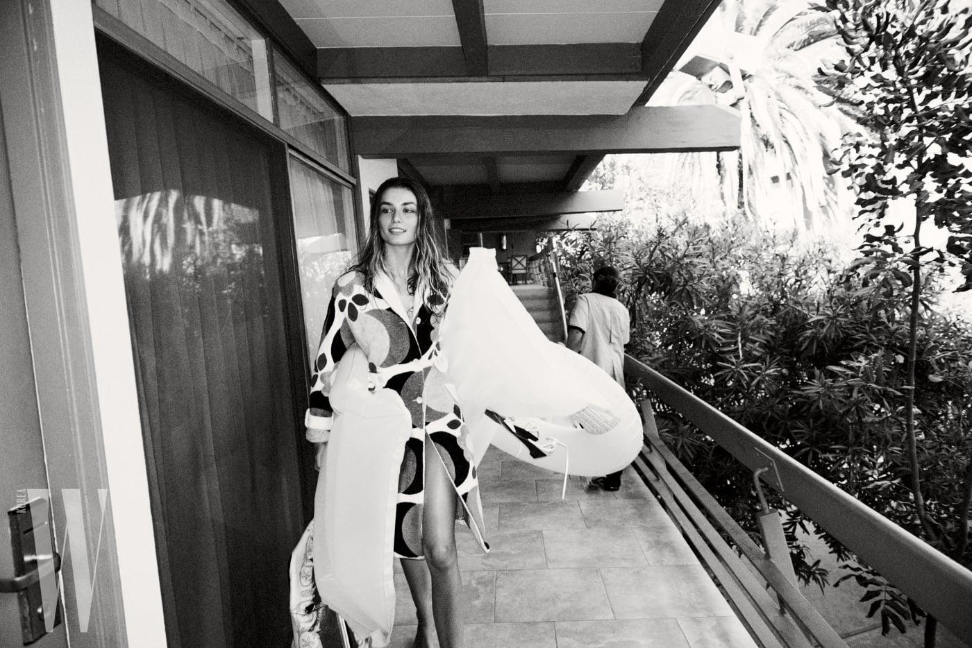로브는 Miu Miu, 블랭킷 백은 Balenciaga, 손에 든 스트랩 슈즈는 Regeneration Vintage by Los Angeles 제품.