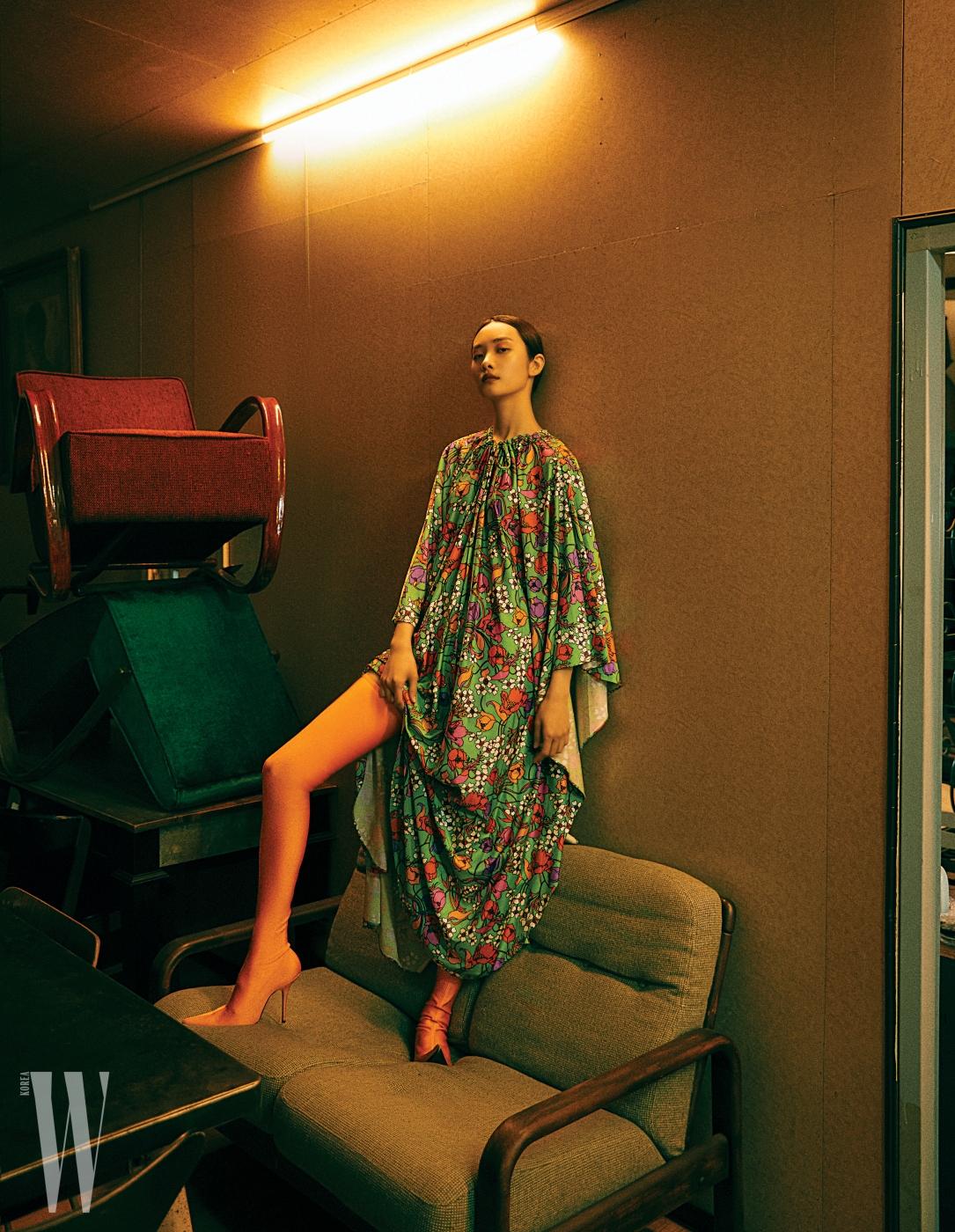 빈티지풍 꽃무늬 드레스, 오렌지 스판덱스 부츠는 Balenciaga 제품. 빈티지 소파는 Tolix 소장품.
