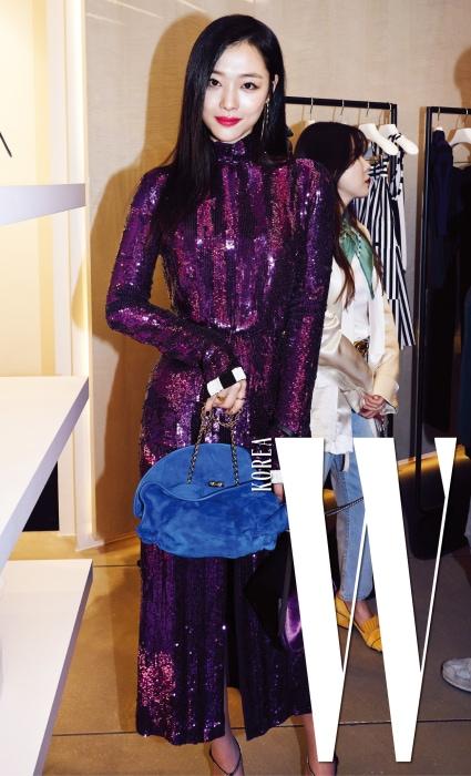 보라색 시퀸 드레스를 입고 등장한 설리. 파란색 쿠티 백을 들고 포즈를 취했다.
