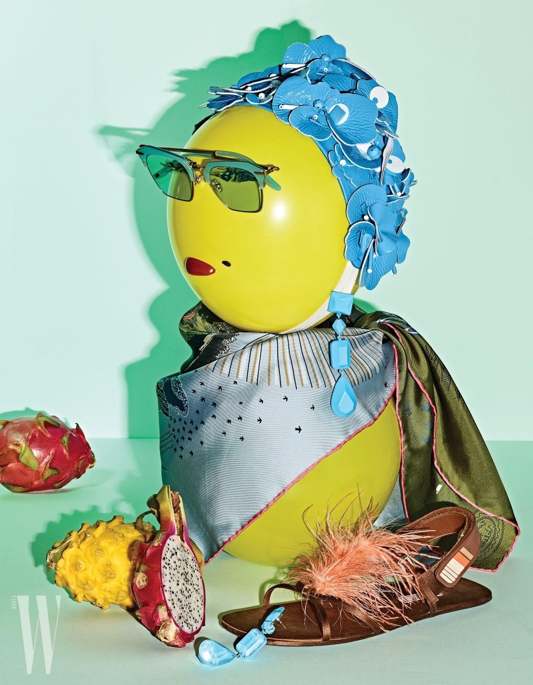 위부터 시계 방향   꽃 모티프의 레트로풍 헤드피스는 Miu Miu, 푸른 원석 장식의 드롭형 귀고리는 Celine, 섬세한 프린트가 돋보이는 실크 스카프는 Valentino Garavani, 타조 깃털 장식이 우아함을 더하는 플랫 샌들은 Prada, 푸른색 셰이딩의 틴트 선글라스는 Front Eyewear 제품.