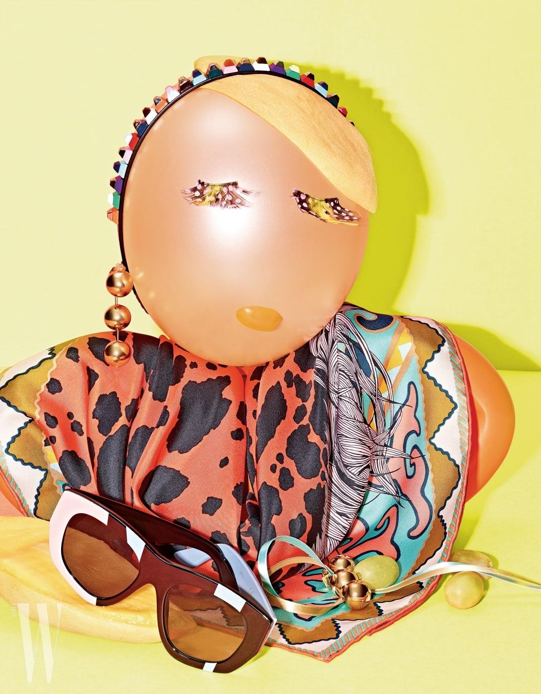 위부터 시계 방향   색색의 스톤 장식 헤드밴드는 Fendi, 강렬한 프린트가 인상적인 실크 스카프는 Hermes, 기하학적 패턴을 더한 프레임의 선글라스는 &otherstories, 금빛 메탈 장식의 드롭형 귀고리는 Balenciaga 제품.