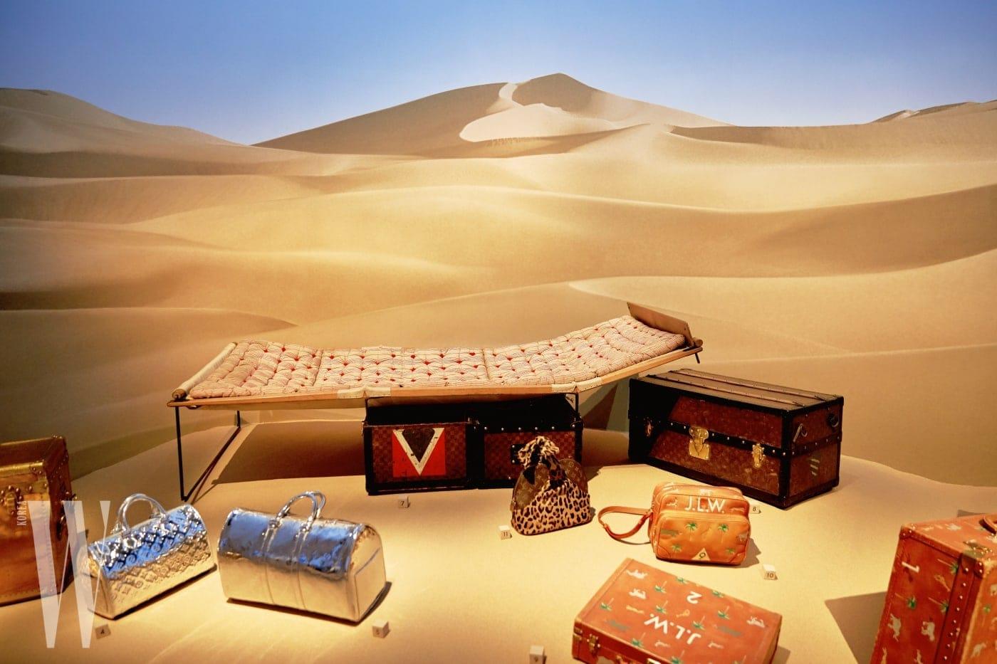 사막 한가운데에 놓인 듯한 연출이 인상적인 트렁크와 여행 가방, 간이 침대.