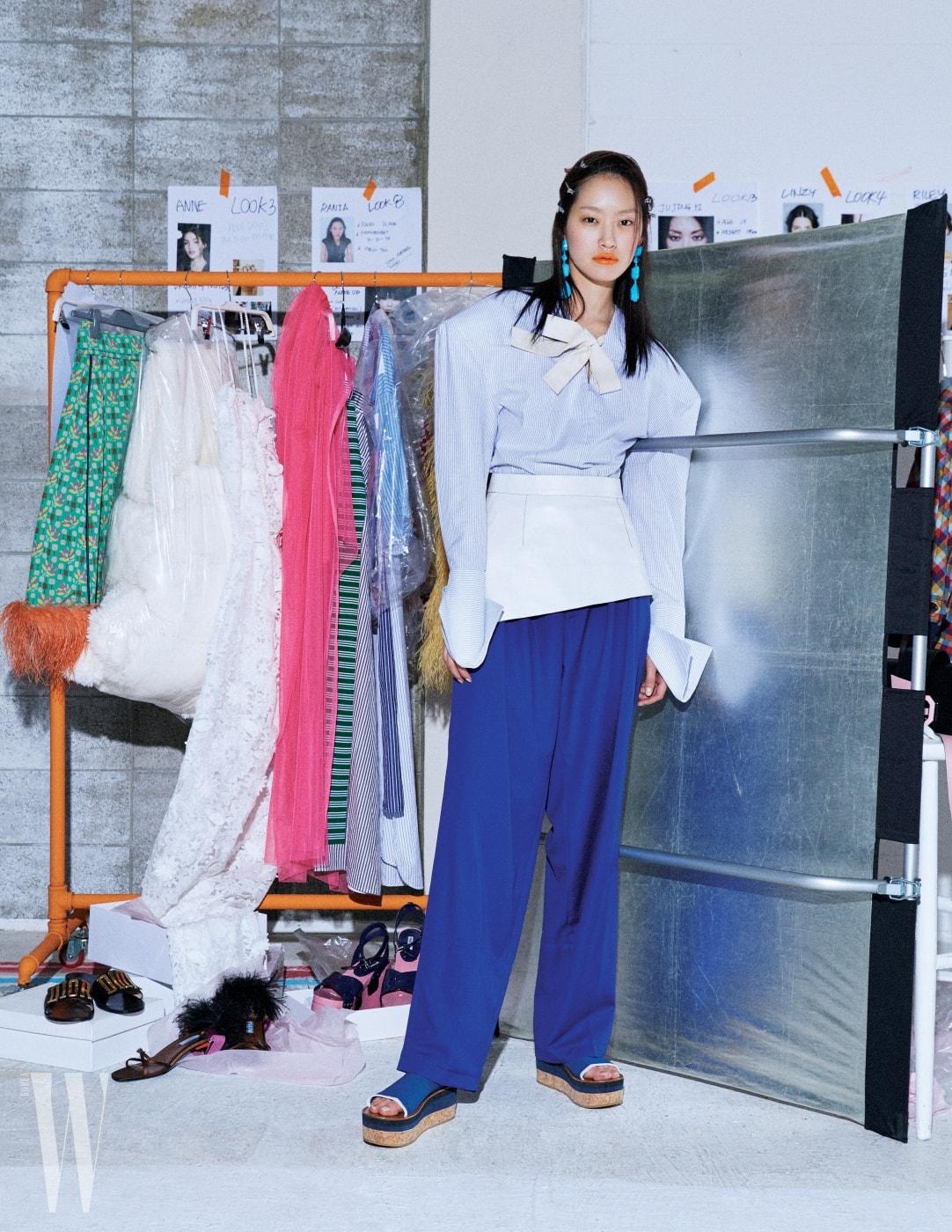 어깨가 강조된 구조적인 셔츠는 자크뮈스 by 10 꼬르소 꼬모 제품. 1백만원대. 파랑 팬츠는 셀린 제품. 가격 미정. 스포티 무드 슈즈는 포츠 1961 제품. 가격 미정. 귀고리는 셀린 제품. 가격 미정.