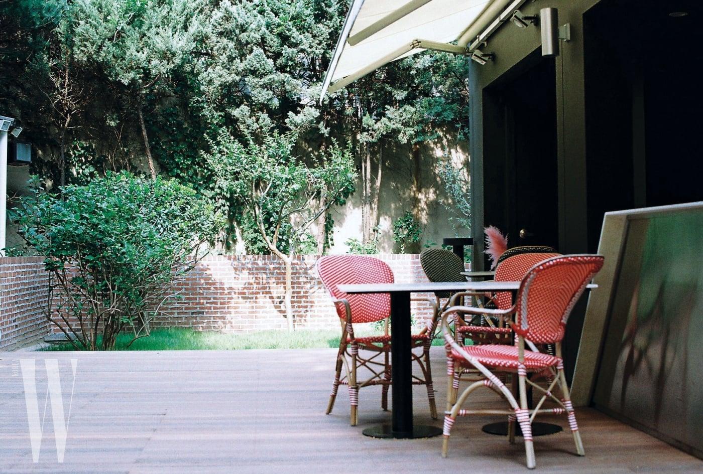 다이닝 공간에서 이어지는 뒤뜰에 들어서면 파리의 카페가 연상되는 푸아투(Poitoux)의 라탄 비스트로 체어가 놓여 있다.