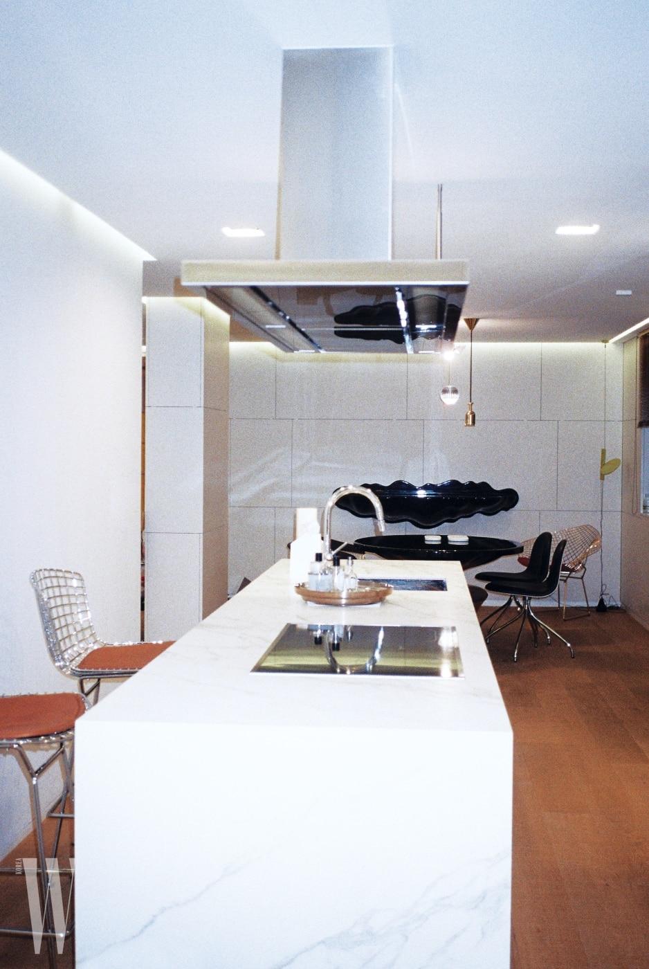 군더더기 없는 흰색과 스틸, 나무 바닥이 어우러진 주방과 다이닝 공간.