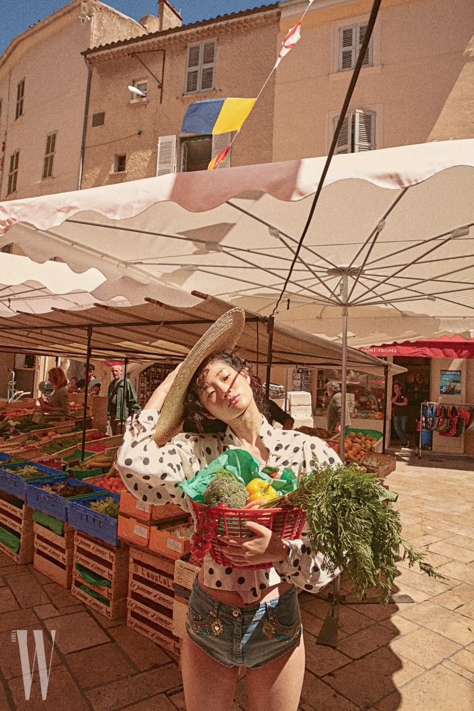 물방울 무늬 블라우스와 모자는 Jacquemus, 데님 쇼츠는 Moschino 제품.