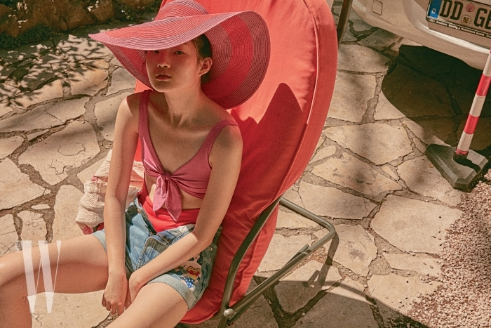 리본 장식 원피스 수영복과 챙이 넓은 모자는 Zara, 원더우먼 캐릭터 데님 쇼츠는 Paul & Joe Sister 제품.