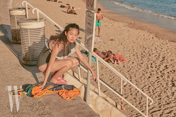 러플 장식 원숄더 수영복은 Lisa Marie Fernandez by Net-a-Porter, 분홍색 플립플롭은 Adidas Originals, 비치 타월은 Hermes 제품.