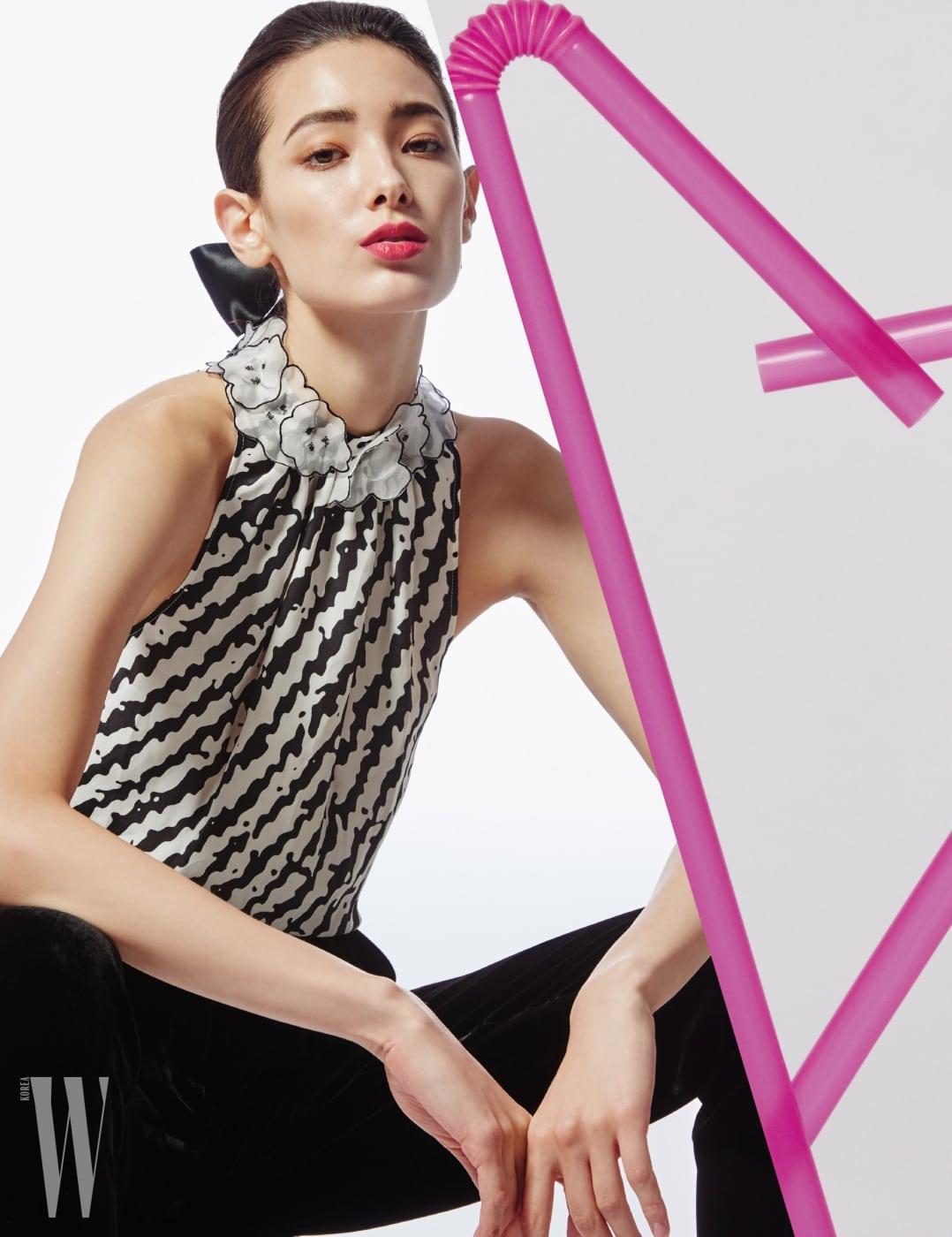 꽃 아플리케를 장식한 그래픽적인 터틀넥 블라우스, 검정 슈트 팬츠는 Emporio Armani 제품.