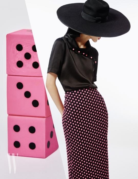 핑크색 단추가 장식된 실크 블라우스, 입체적인 느낌의 도트무늬 펜슬 스커트, 큼직한 모자는 모두 Emporio Armani 제품.