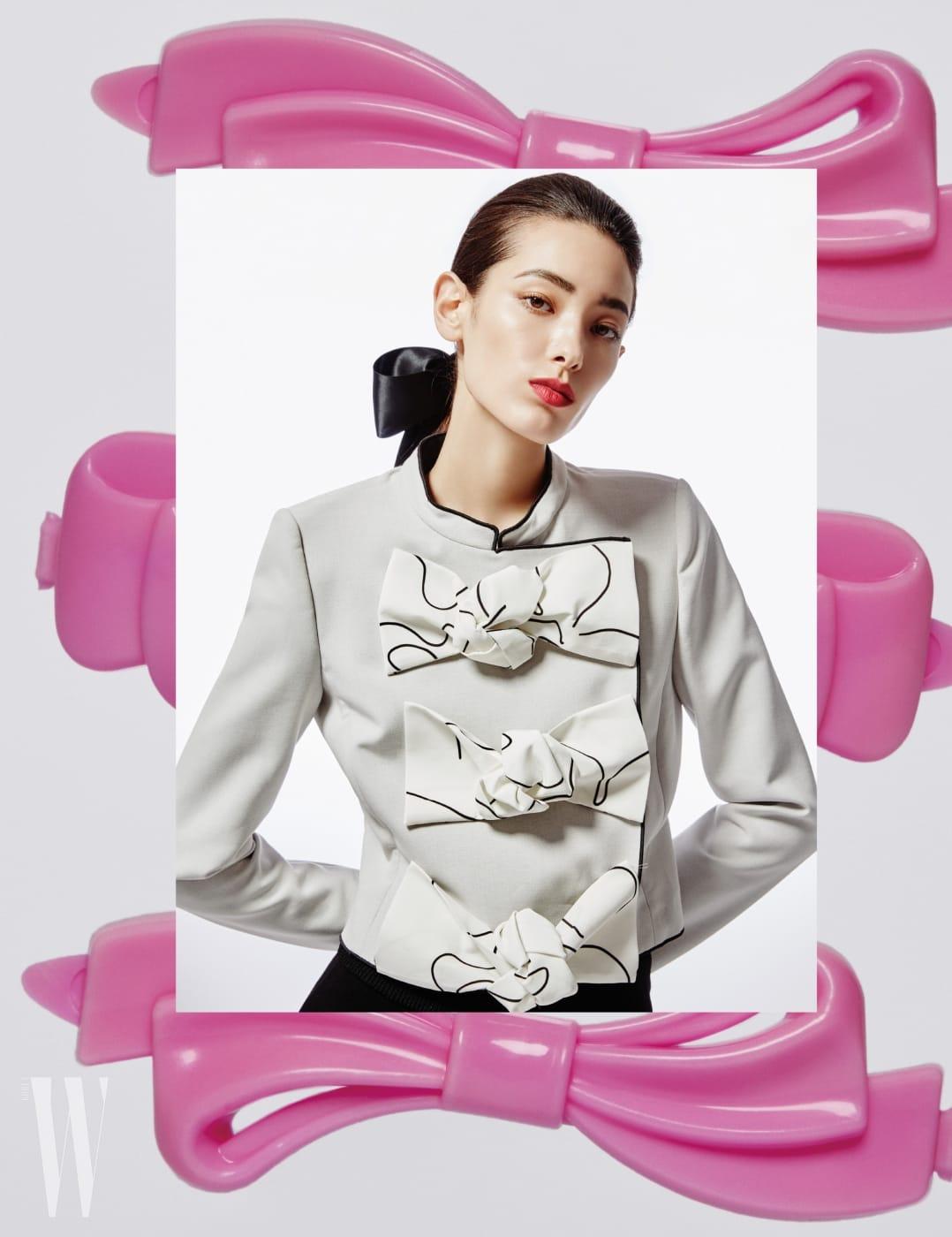 큼직한 리본이 장식된 차이니스칼라 재킷, 검정 팬츠는 Emporio Armani 제품.