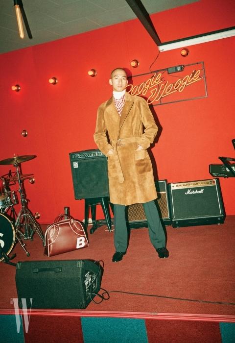 아이보리색 터틀넥, 빨간색 체크 셔츠, 스웨이드 코트, 녹색 팬츠, 가죽 더플 백은 모두 BALLY 제품.