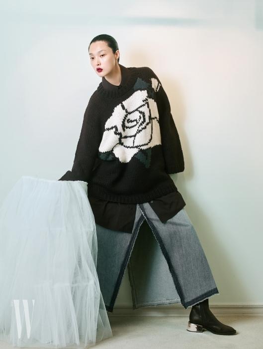 큼직한 장미 무늬 니트 스웨터, 안에 입은 검은색 셔츠, 슬릿이 깊게 들어간 데님 롱스커트, 메탈 굽 장식의 앵클부츠는 모두 MM6 제품.