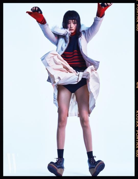 목 부분에 라쿤퍼가 장식된 점퍼와 줄무늬 니트 터틀넥, 아이보리 색상의 주름 스커트, 핑거리스 장갑, 아웃도어 스타일의 플랫폼 힐 슈즈는 모두 Moncler 제품.