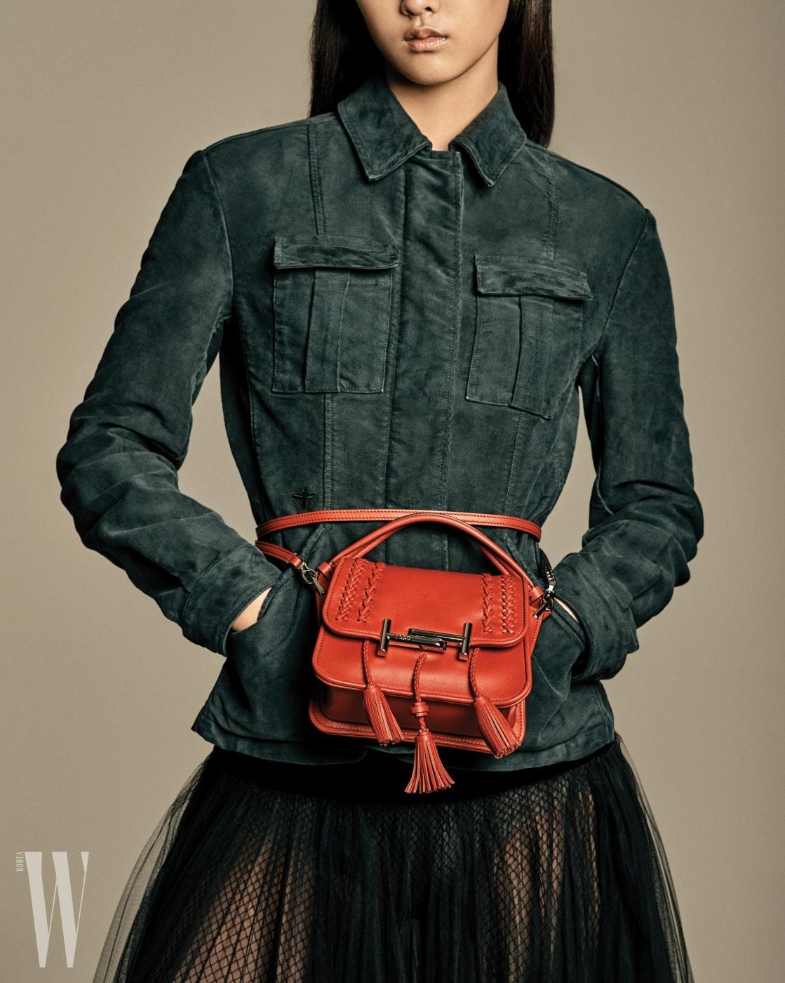 허리에 포인트로 착용한 태슬 장식 미니 백은 토즈 제품. 가격미정. 검은색 데님 재킷, 풍성한 샤 스커트는 디올 제품. 가격 미정.
