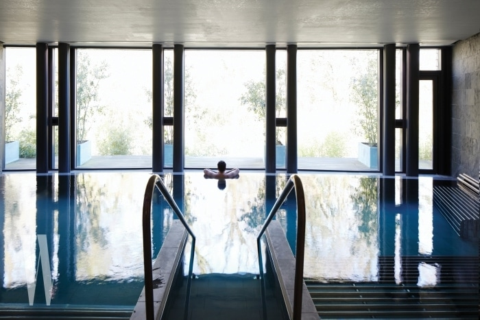 Man relaxing in modern, country setting, indoor spa treatment pool, looking out window
