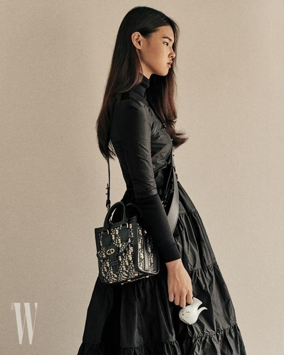 검정 터틀넥 톱과 위에 입은 오프숄더 드레스, 로고 장식의 미니 숄더백은 모두 디올 제품. 가격 미정.