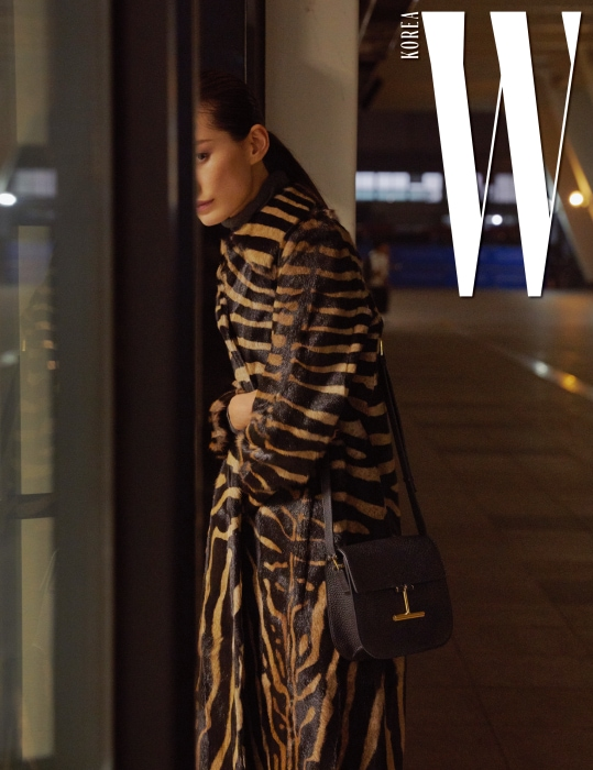 강렬한 얼룩말 패턴이 돋보이는 염소털 소재 코트와 베이식한 검정 터틀넥 스웨터, 미니 사이즈 '타라' 백은 모두 Tom Ford 제품.