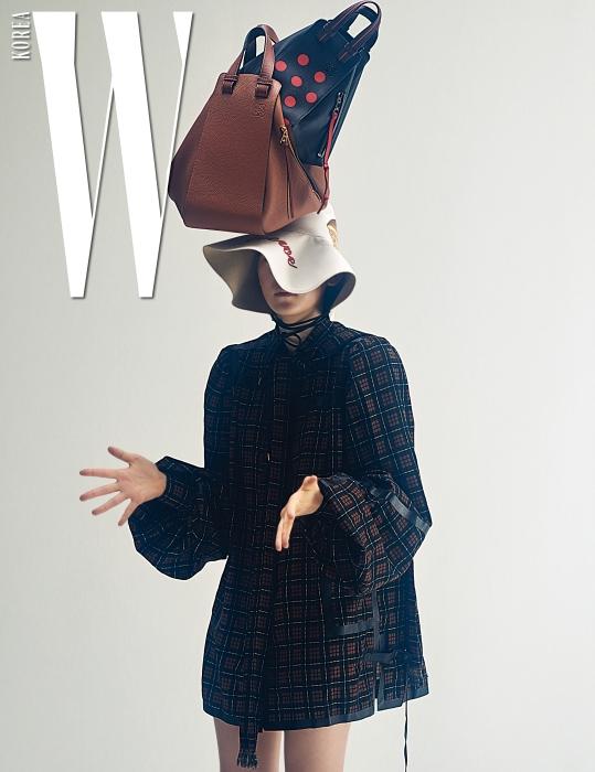 풍성한 소매가 인상적인 체크무늬 미니 드레스, 팝아트적인 프린트의 토스트 모자, 머리에 쌓아 올린 갈색 해먹 백, 빨강 도트무늬 해먹 백은 모두 Loewe 제품.