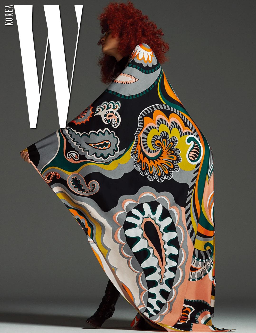 검은색의 꼭 끼는 실루엣과 페이즐리 패턴의 박시한 실루엣으로 좌우가 상반된 디자인이 특징인 드레스와 페이턴트 소재의 갈색 슈즈는 Emilio Pucci 제품.