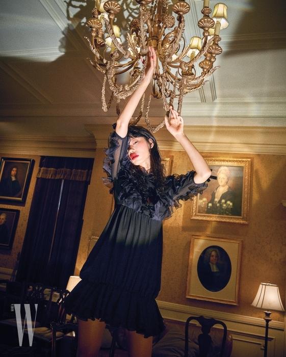 소매와 몸통을 장식한 러플 장식이 특징인 검은색 미니 드레스는 Giambattista Valli 제품.