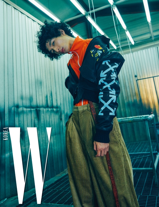가죽 소재의 항공점퍼와, 오렌지색 트랙 톱 재킷, 통이 넓은 코듀로이 팬츠, 허리에 묶은 벨트, 검은색 스니커즈는 모두 Off-White 제품.