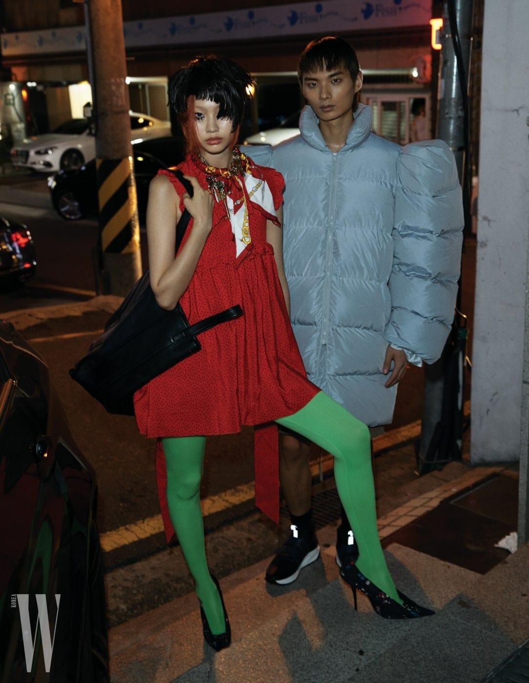 정호연이 입은 베이비돌 드레스, 타이츠, 열쇠 목걸이, 스카프 목걸이, 슈즈, 커다란 런드리 가방은 모두 Balenciaga 제품. 송준호가 입은 패딩 재킷은 Blindness, 슈즈는 Ports 1961 제품.