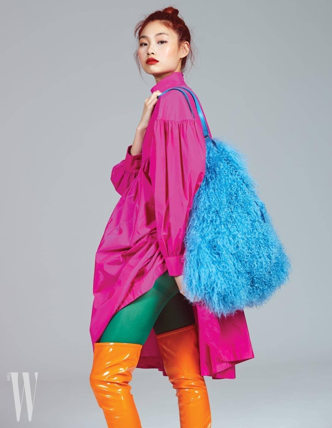 팔에 풍성한 볼륨이 잡힌 핫 핑크색 베이비돌 드레스는 겐조 제품. 가격 미정. 페이턴트 소재의 주황색 사이하이 부츠는 루이 비통 제품. 2백만원대.  하늘색의 양털 숄더백은 니나리치 제품. 4백30만원. 초록색 스타킹은 스타일리스트 소장품.