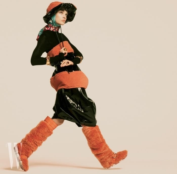 광택이 도는 드레스와 모자는 Marni, 터틀넥은 Salvatore Ferragamo, 스카프는 Gucci, 커다란 골드 링과 브레이슬릿은 Sonia Boyajian Jewelry, 주황색 양털 부츠는 Miu Miu 제품.