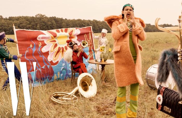 에코 퍼 칼라 장식 코트, 주얼 장식 니트 톱, 니트 팬츠, 크리스털 버클 장식 초록색 헤드피스, 오른쪽에 걸려 있는 퍼 스트랩 파이톤 벨트 마텔라쎄 미니 백은 모두 Miu Miu 제품.