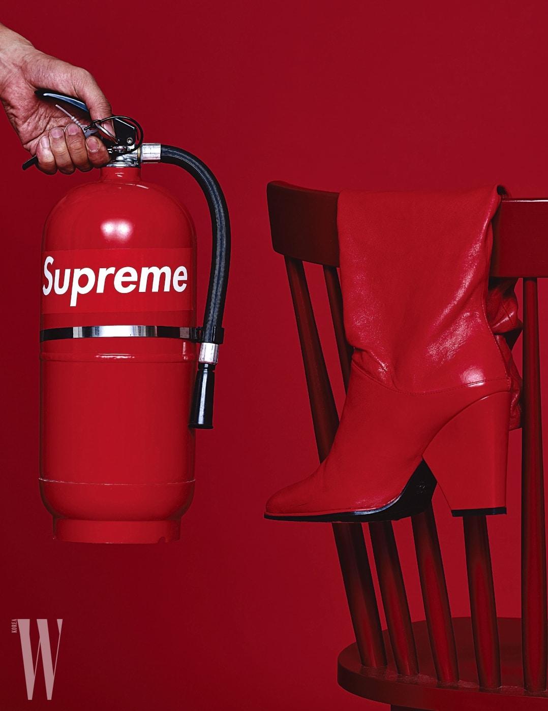 슈프림 스티커를 부착한 수화기 옆에 놓인 붉은색 부츠는 스튜어트 와이츠먼 제품. 가격 미정.