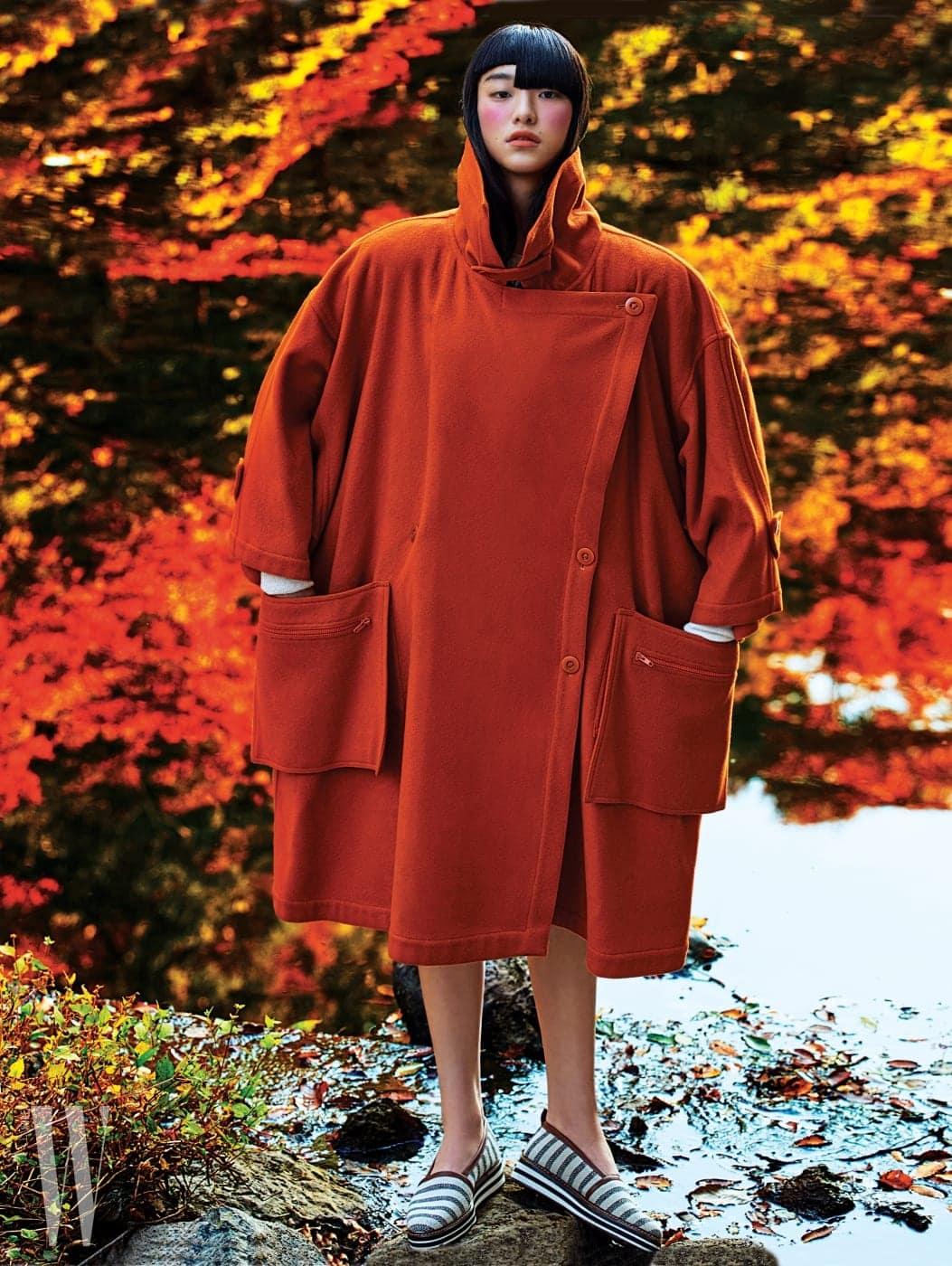1980년대 실루엣의 오버사이즈 코쿤 코트. 여유로운 실루엣과 큼직한 주머니 장식이 당시의 개성을 드러낸다. 흰색 니트 톱과 줄무늬 슬립온 슈즈는 Max Mara 크루즈 컬렉션 제품.