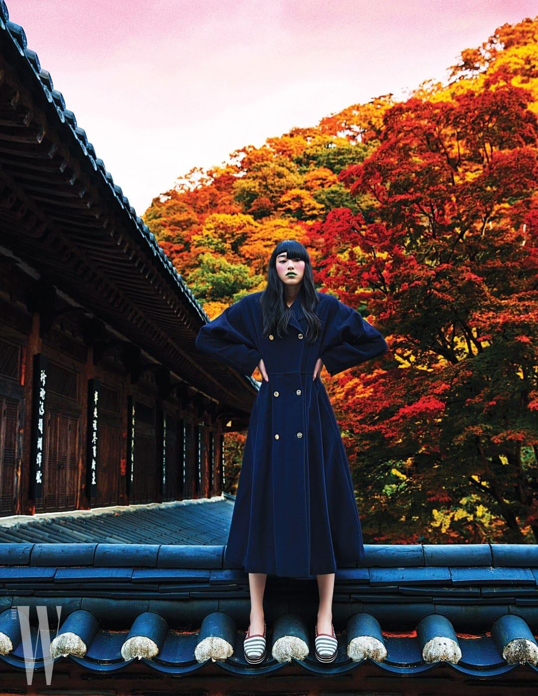 강인한 밀리터리 무드와 코트 드레스 형태의 우아한 드레이핑이 결합된 코트. 여성스러운 실루엣과 금빛 단추 장식이 돋보인다.