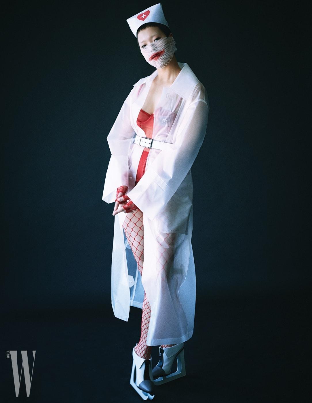 모델 이민조가 입은 플라스틱 카 코트는 Burberry, 안에 입은 빨강 뷔스티에는 Laperla, 하얀색 가죽 벨트는 Levi's, 조형적인 슈즈는 Tom Browne 제품.