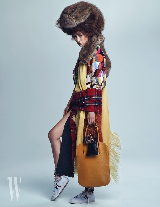 머리에 얹어 연출한 두툼한 퍼 가방은 Simone Rocha by Boon the Shop, 컬러 블록 니트 카디건은 Prada, 노란색 타조 깃털 장식 머플러는 N˚21 by Boon the shop, 허리에 두른 주황색 니트 케이프는 Sonia Rykiel, 클래식 체크 패턴 목도리는 Burberry, 노란색 가죽 소재 가방은 Nina Ricci, 체인과 깃털 장식이 독특한 립스틱 케이스, 검은색 미니 백은 Valentino Garavani, 양말은 Burberry, 스니커즈는 Celine 제품 .