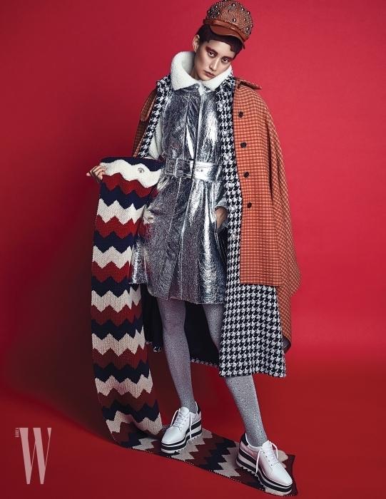스터드 장식 가죽 모자는 Miu Miu, 어깨에 두른 오렌지색 케이프는 Sonia Rykiel, 하운즈투스 체크무늬 코트와 메탈릭 실버 코트, 레깅스는 모두 Chanel, 플랫폼 슈즈는 Stella McCartney, 지그재그 무늬의 목도리는 Moncler 제품.