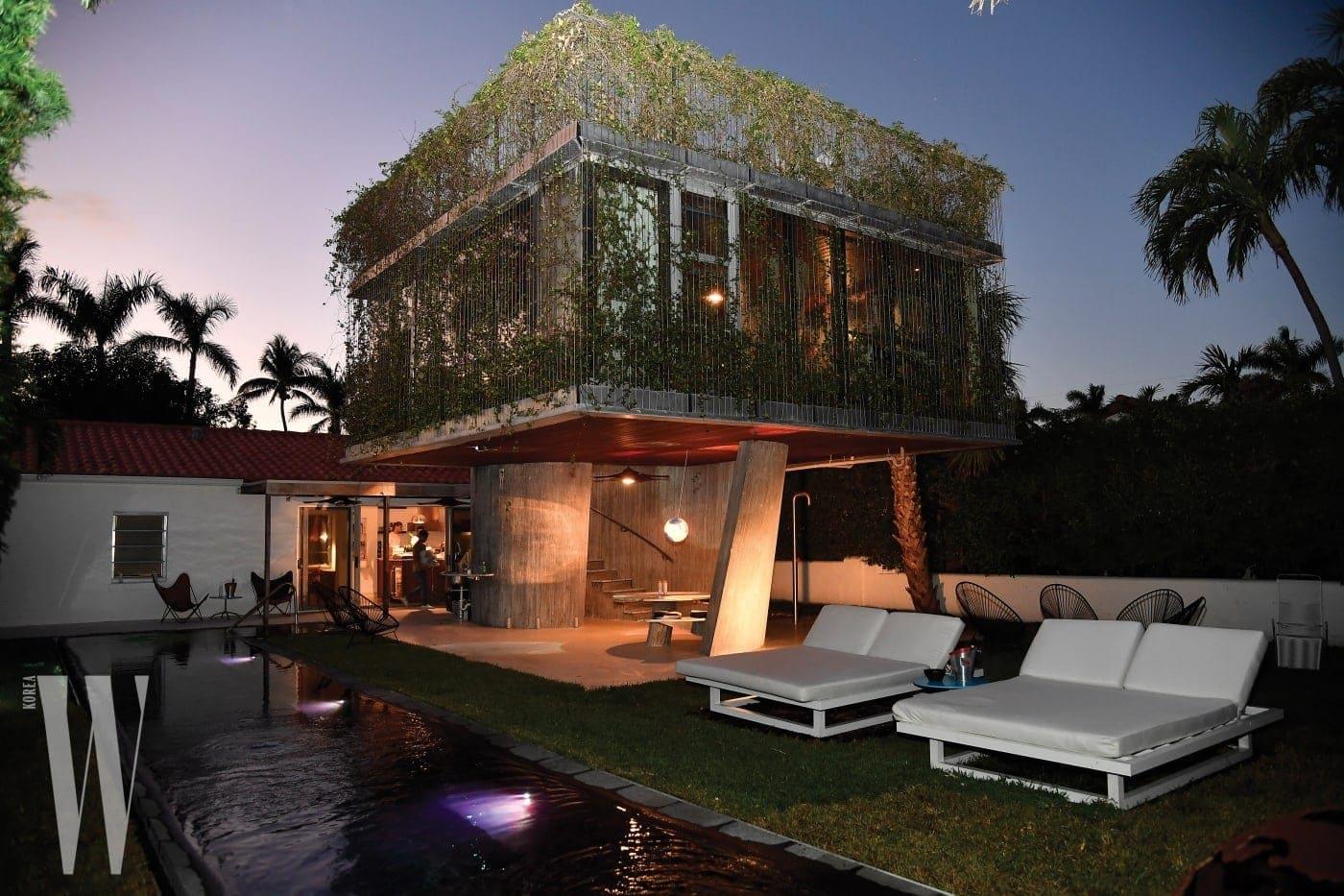 환상적인 저녁에 풀 파티가 펼쳐진 건축가 크리스천 바스만의 선 배스 하우스 전경.