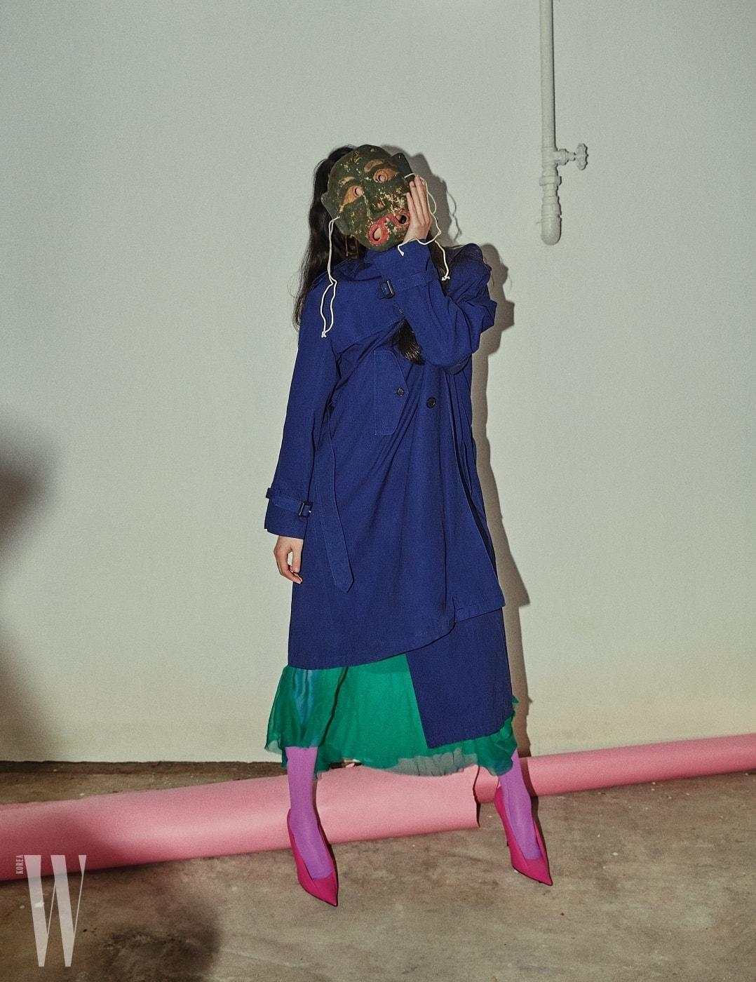 네이비색 트렌치코트, 실크  원피스, 분홍색 타이츠와 가죽 펌프스, 골드 이어링은모두 Balenciaga 제품.