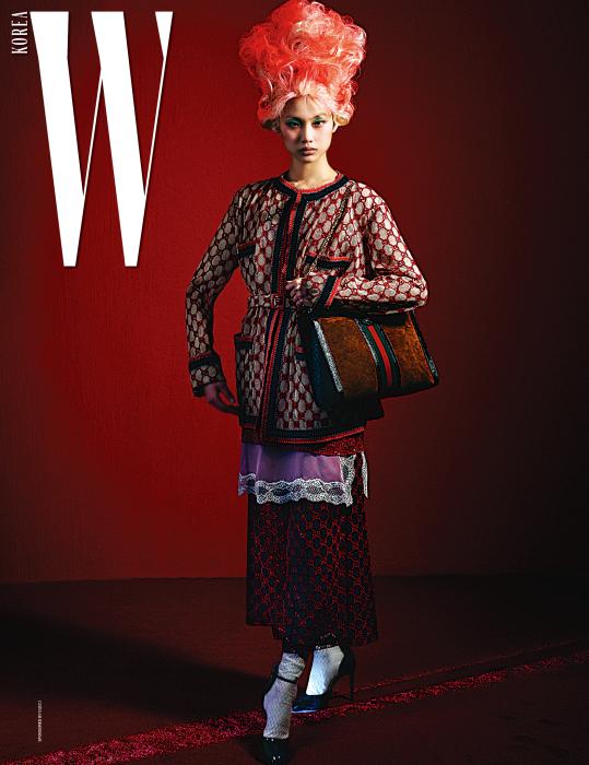 로고 장식의 자수 재킷, 안에 입은 빨강 로고 장식의 자수 톱, 연보라색 레이스 슬리브리스 톱, 빨강 로고 장식 자수 스커트, 니트 양말과 검정 페이턴트 슈즈는 모두 Gucci 제품.