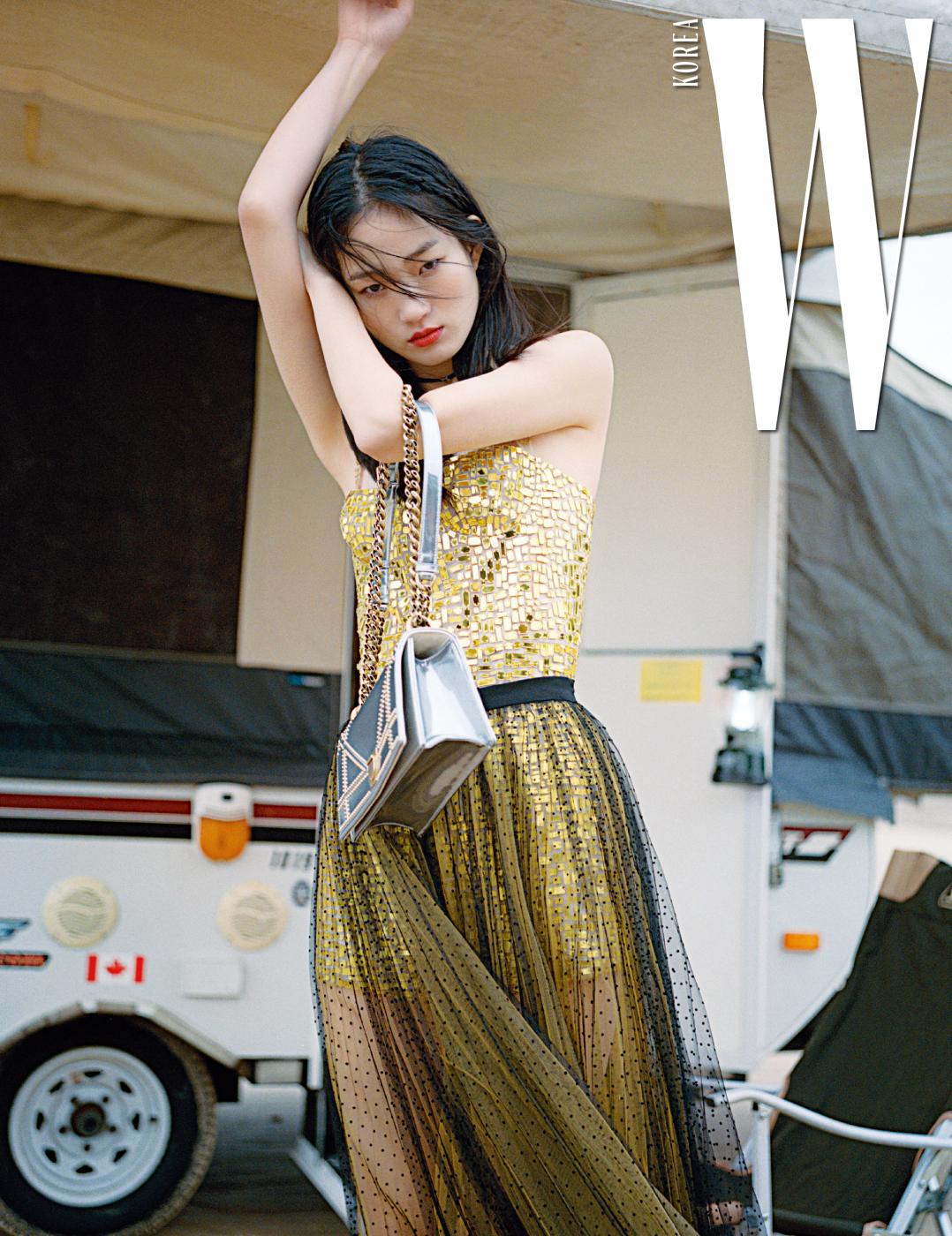반짝이는 유리 조각을 이어 붙인 듯한 점프슈트와 샤 스커트, 핸드백은 모두 Dior 제품.