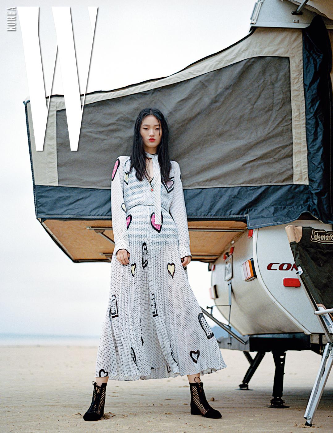 하트 무늬가 새겨진 리본 장식 드레스와 레이스업 슈즈, 목걸이는 모두 Dior 제품.