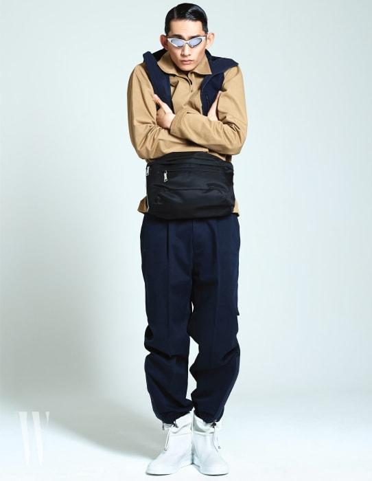 개버딘 소재 오버사이즈 셔츠, 크롭트 후디 베스트, 넓은 팬츠, 끈 장식 부츠는 지 제냐, 허리에 찬 벨트 백은 프라다, 메탈릭한 선글라스는 루이 비통 제품.