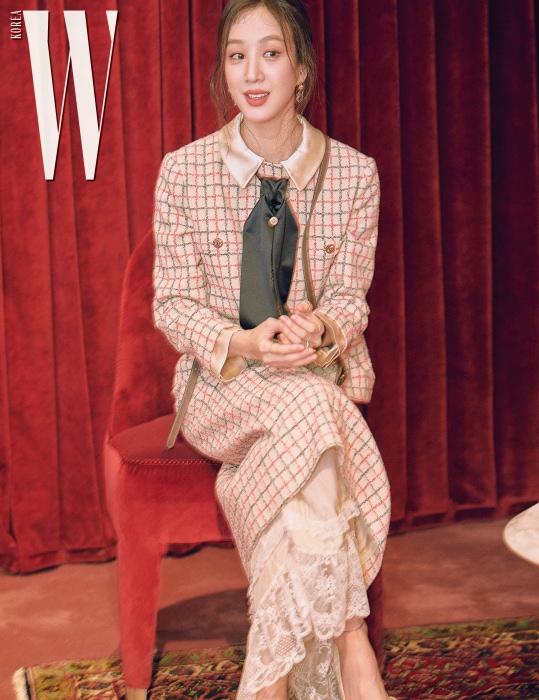 려원은 옅은 색상의 체크무늬 재킷에 레이스 스커트와 보 장식 슈즈를 매치했다.