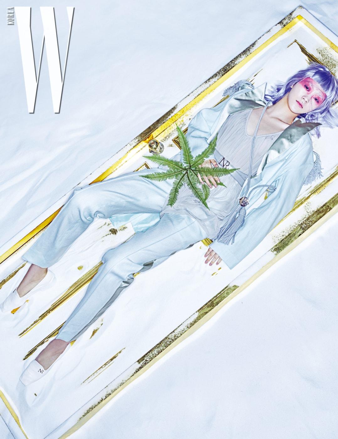섬세한 광택의 새틴 라펠이 돋보이는 테일러드 재킷, 시폰 튜닉, 이니셜 버클 장식의 가죽 벨트, 시가렛 팬츠, 목걸이처럼 연출한 태슬 장식 가죽 벨트, NR 이니셜 장식의 로퍼는 모두 Nina Ricci 제품.