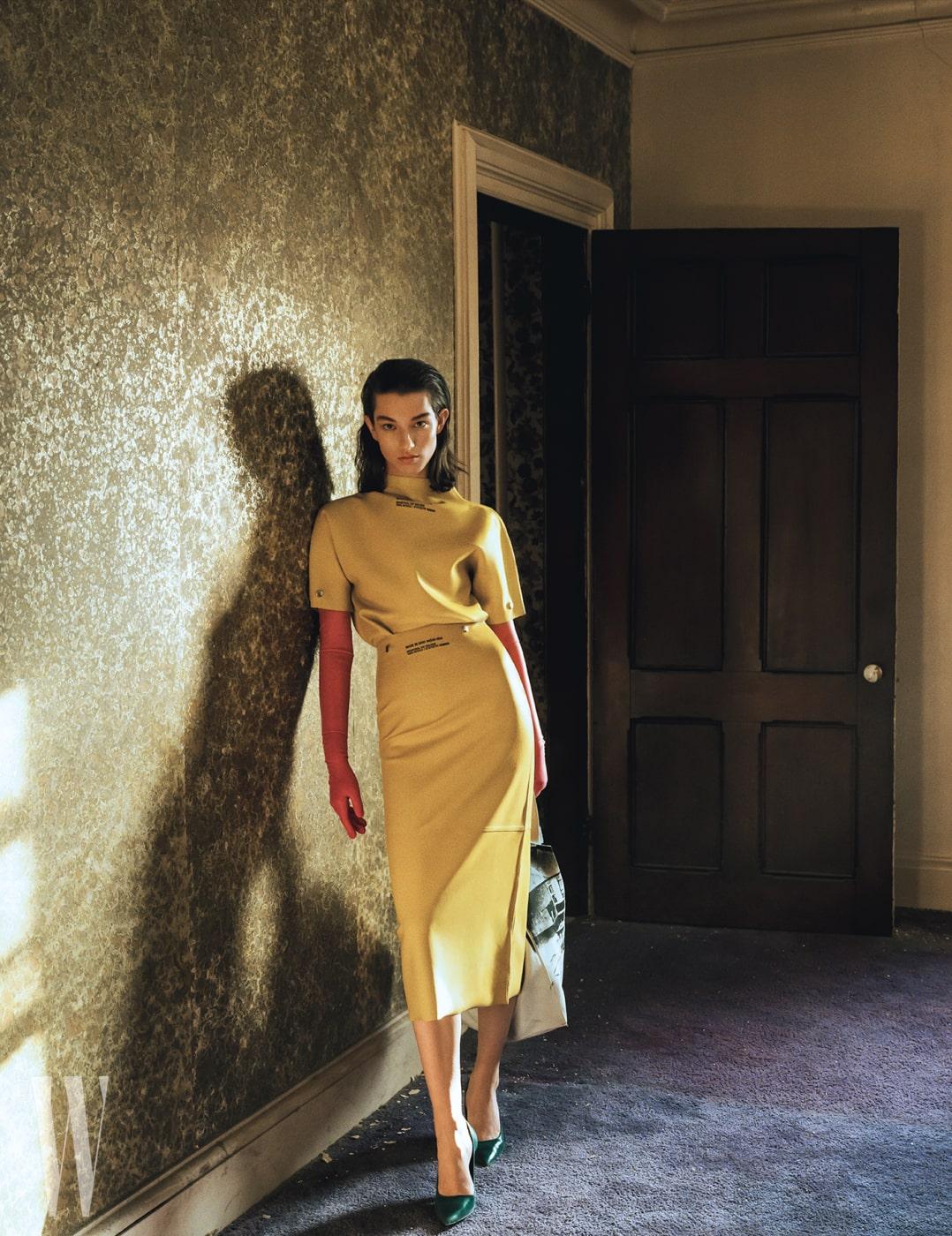 노란색 러버 소재 톱과 시가렛 스커트, 분홍색 라텍스 소재의 긴 장갑, 초록색 가죽 펌프스, 숄더백은 모두 Calvin Klein 205W39NYC 제품.